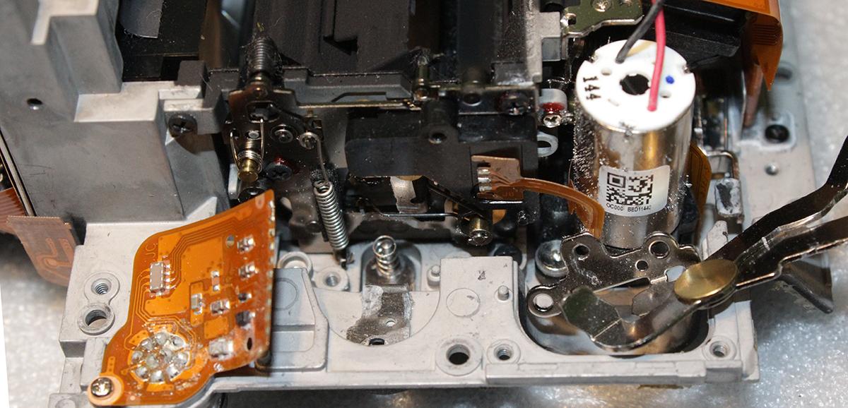 Лапка со штифтом механизма блокировки-разблокировки объектива в Nikon D4